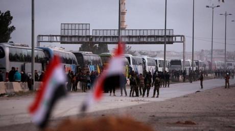 Un convoi de bus évacue des combattants armés de la ville de Harasta dans la Ghouta orientale, le 22 mars