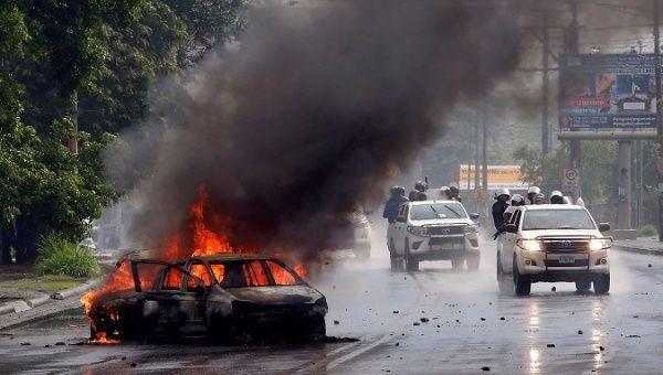 Des policiers anti-émeutes passent devant une voiture en feu lors d'affrontements avec les manifestants antigouvernementaux à Managua, au Nicaragua, le 28 mai 2018.